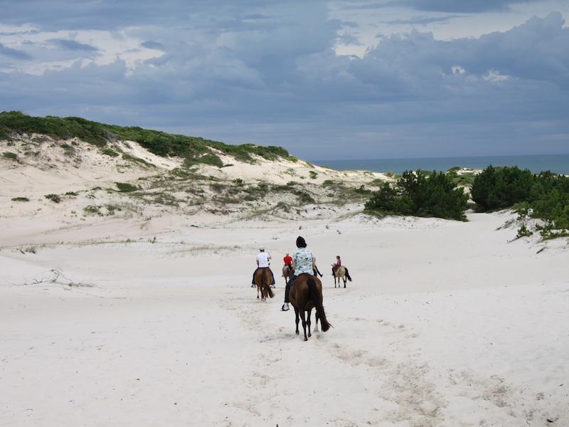Reiten am weiten Strand von Moçambique